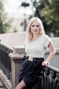 Fashion street style portret van mooie vrouw met verbazingwekkende lange blonde haren, stijlvolle schattige outfit