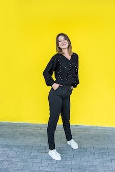 Fashional portret van mooie dame in de buurt van gele muur. levensstijl