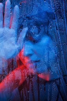 Fasion en creativiteit. studio opname in donkere studio met neonlicht. portret van mooi meisje achter nat glas