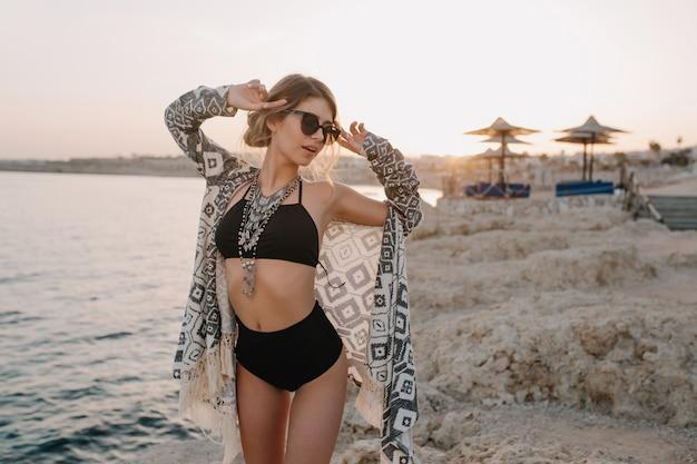 Fasionable model poseren op strand, zonsondergang. sexy meisje draagt zwarte bikini, zwembroek met hoge taille, vest, cape met versieringen, prachtig strand, zee, rots.