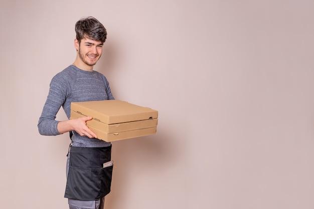 Fast-food bezorger met pizzadozen in zijn handen bezorgt de bestelling voor bezorging, gekleed in uniform en glimlachend