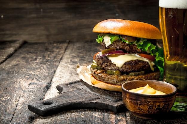 Fast food. een grote burger met rundvlees en een glas bier. op een houten achtergrond.