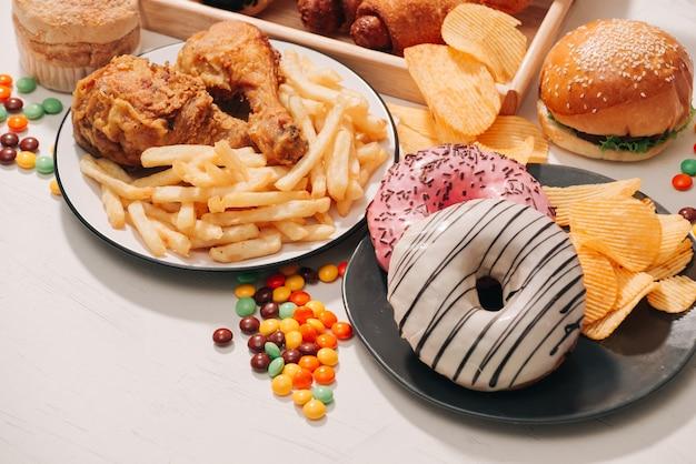 Fast food en ongezond eten concept - close-up van fast food snacks en cola drinken op witte tafel