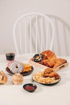 Fast food en ongezond eten concept - close-up van hamburger of cheeseburger, gefrituurde inktvisringen, frietjes, drankje en ketchup op houten tafel