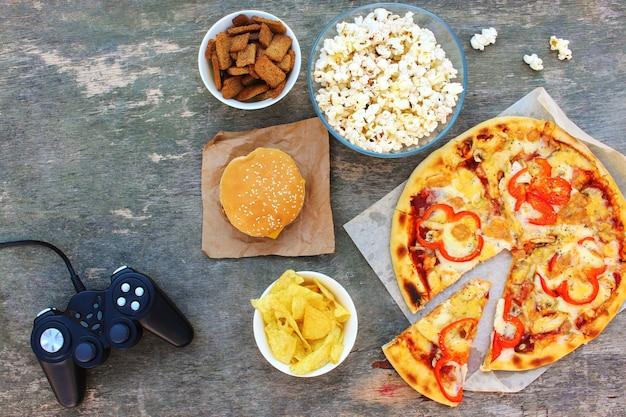 Fast food en video game controller op oude houten achtergrond. concept van junk eten. bovenaanzicht. plat leggen.