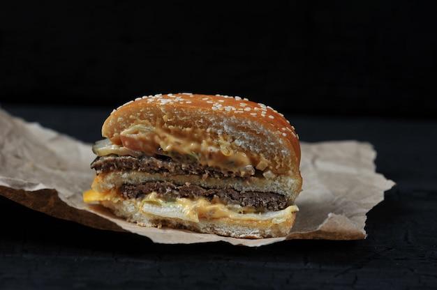 Fast food - in tweeën gesneden hamburger met kaas en rundvlees op kraft papier op zwarte houtskool achtergrond