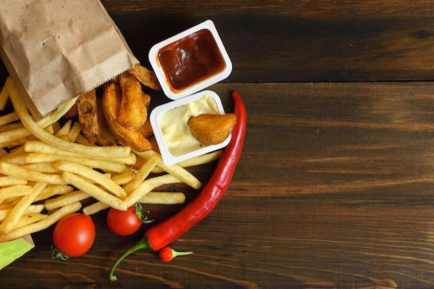 Fast food producten: frietjes met saus en voedselingrediënten op donkere houten tafel met kopie ruimte, bovenaanzicht