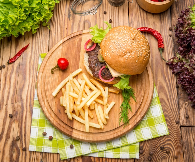 Fast-food schotel bovenaanzicht. vleeshamburger in ambachtelijk papier en chips. samenstelling weghalen.