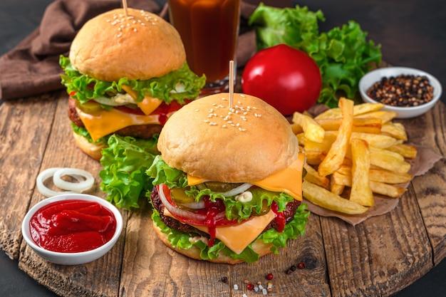 Fast food. twee hamburgers met rundvlees en verse groenten op een bruine achtergrond. horizontale weergave.