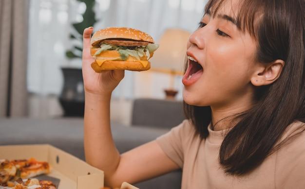 Fastfood afhaalmaaltijden thuis. burger eten bij afhalen en bezorgen. aziatische vrouw levensstijl in woonkamer. social distancing en het nieuwe normaal.
