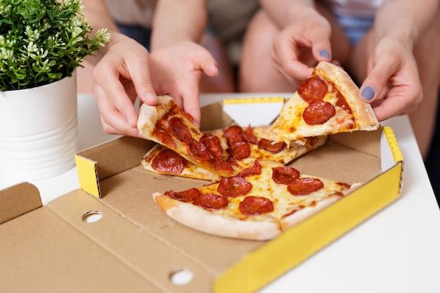 Fastfood - close-up van vrouwelijke handen die pepperoni-pizzaplakken uit een kartonnen doos nemen