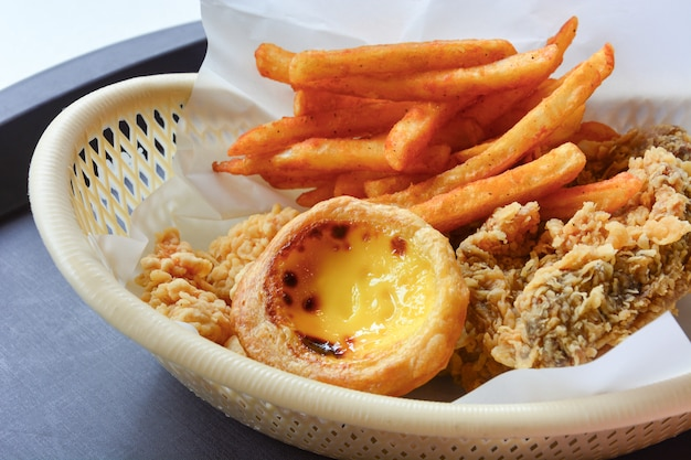 Fastfood in mandje, krokant gebakken kip, gefrituurd en eiertaart