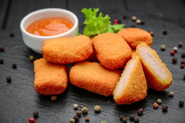 Fastfood kipnuggets met ketchup, tegen een donkere achtergrond