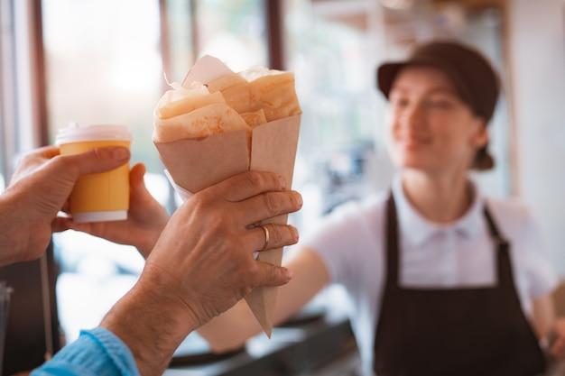 Fastfood kopen. een pannenkoek met vulling en een papieren beker met koffie in de handen van een vrouwelijke verkoper en een klant in de cafetaria. afhaalmaaltijden.