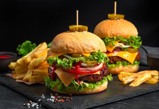 Fastfood, lunch met hamburgers en frietjes. twee grote hamburgers met vlees, groenten, kruiden en kaas op een zwarte achtergrond.