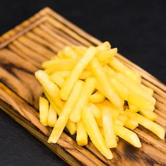 Fastfood-menu. bovenaanzicht van traditionele gezouten frietjes op rustieke houten bord.