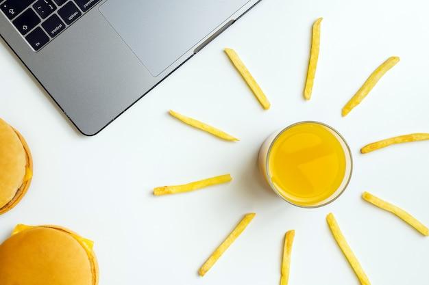 Fastfood op het werk snacken. laptop, hamburger en friet op de werkplek.