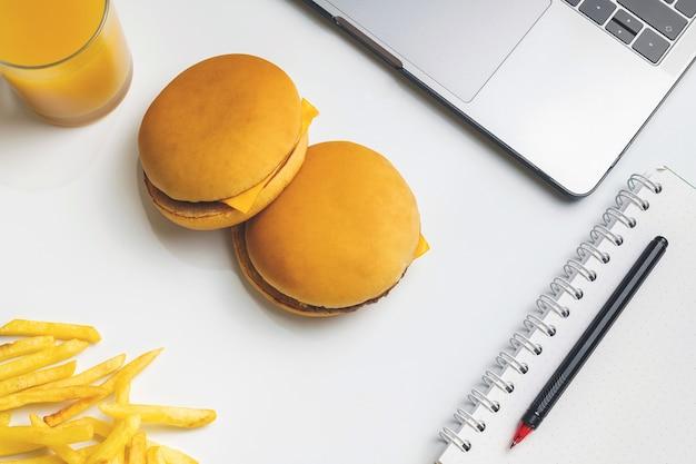 Fastfood op het werk snacken. laptop, twee hamburgers en friet op de werkplek.