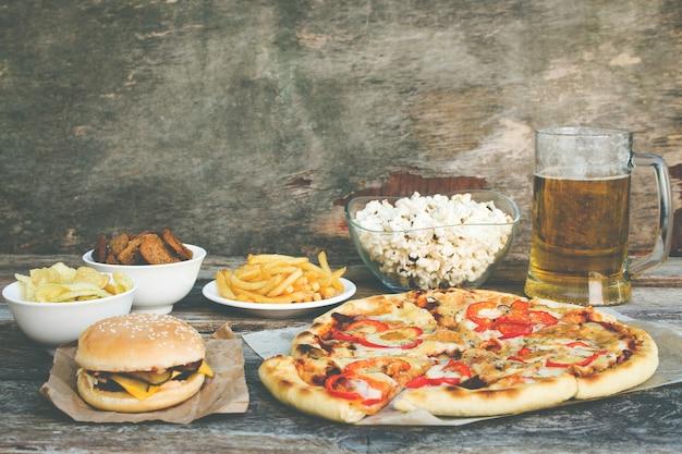 Fastfood op oude houten achtergrond. concept van junk eten. getinte afbeelding.