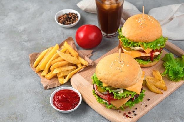 Fastfood, twee grote hamburgers met frietjes, saus en cola op een grijze achtergrond. ruimte kopiëren.