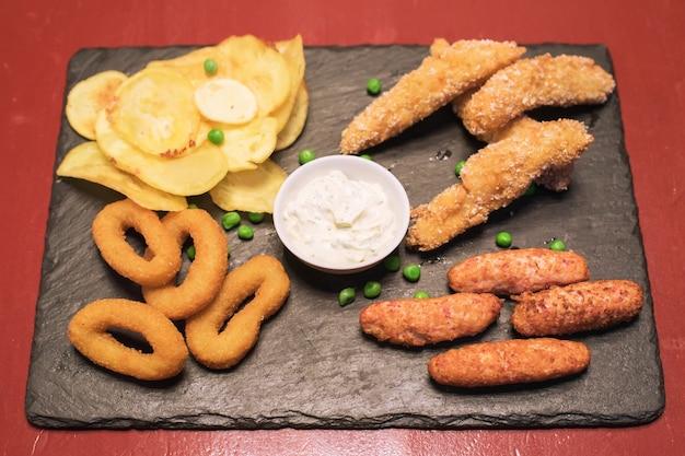 Fastfood uienringen aardappelen en gebakken kippensaus op een donkere tafelbladweergave