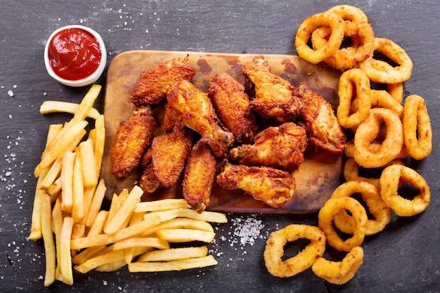 Fastfoodproducten: uienringen, frietjes en gebakken kip op donkere tafel, bovenaanzicht