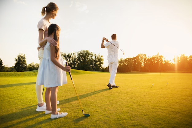 Father takes golf shot happy family of players.