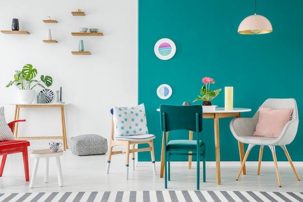 Fauteuil en stoel aan houten tafel met roze bloemen tegen groene muur in appartement interieur