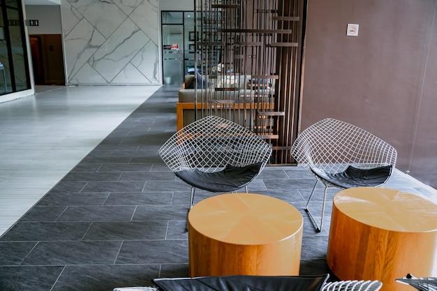 Fauteuil op tapijt naast bank met planten in witte loft interieur met houten bank.