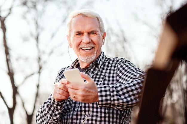 Favoriet liedje. lage hoek van vrolijke senior man grijnzend naar de camera en luisteren naar muziek