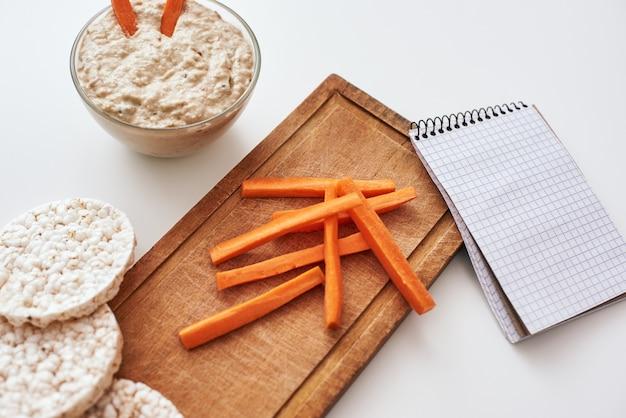 Favoriet veganistisch gerecht. hummus met worteltjes. bovenaanzicht van humus met broden evenwicht geïsoleerd op een witte achtergrond. een recept schrijven op notebook