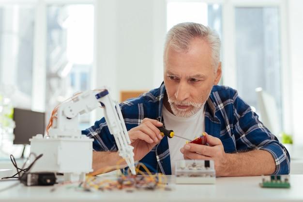 Favoriete bezigheid. ernstige slimme ingenieur die een robot maakt terwijl hij aan zijn project werkt