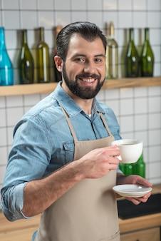 Favoriete drankje. positieve jonge vrolijke ober die zich gelukkig voelt terwijl hij aan het werk is en zijn favoriete koffie drinkt voordat hij naar zijn bezoekers gaat