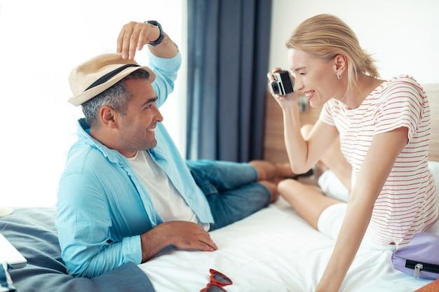 Favoriete fotograaf. vrolijke man probeert een strohoed te poseren voor zijn vrouw met een camera die samen op het bed ligt.