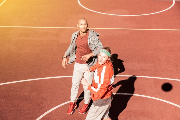 Favoriete game. leuke sportieve mannen die samen basketballen tijdens een wedstrijd