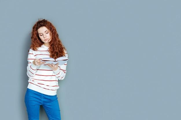Favoriete hobby. aantrekkelijke aardige intelligente vrouw die zich tegen blauwe achtergrond bevindt en een verhaal leest terwijl zij een boek vasthoudt