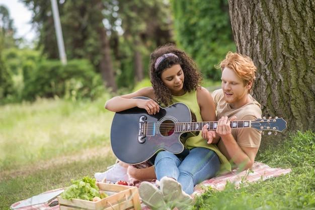 Favoriete hobby. attente roodharige man die meisje met lang krullend haar leert gitaar te spelen met rust op picknick in de natuur op zomerdag