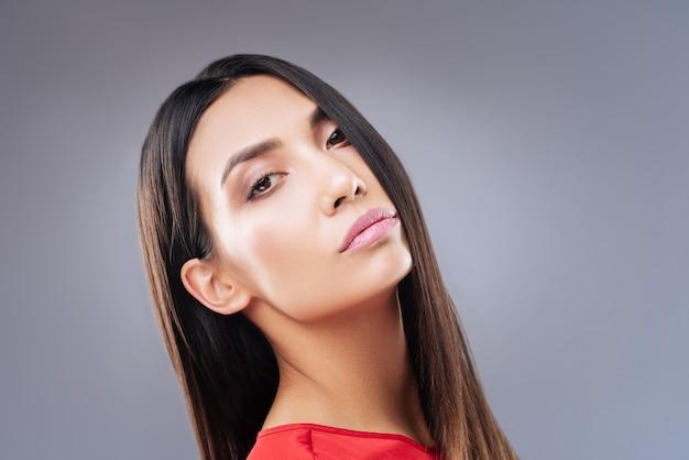 Favoriete lippenstift. verbazingwekkend emotioneel portret van een jonge mooie vrouw met bruine ogen en roze lippen die tegen de blauwe muur staan en er vredig en kalm uitzien