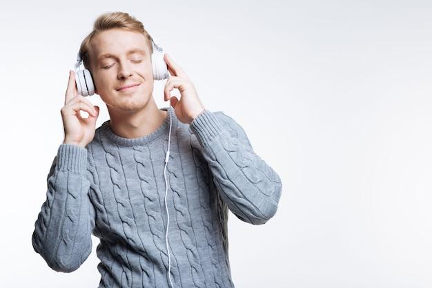 Favoriete muziek. mooie blonde jongeman in een grijze trui, luisteren naar de muziek in een witte koptelefoon terwijl hij zijn ogen dicht houdt