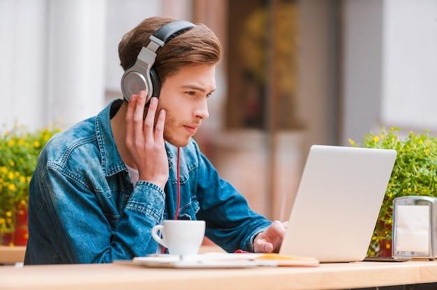 Favoriete muziek verhoogt mijn productiviteit. ernstige jonge man in koptelefoon die op laptop werkt