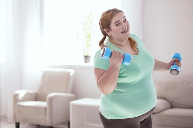 Favoriete oefening. glimlachende roodharige vrouw die naar rechts leunt tijdens het doen van oefeningen met halters