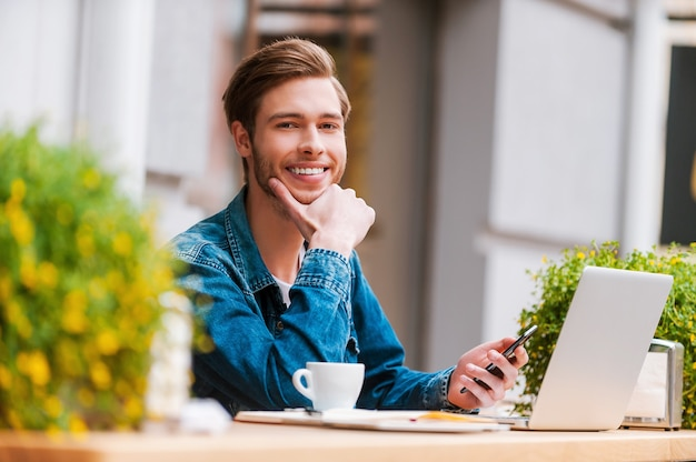Favoriete plek voor koffie en wifi. gelukkige jonge man die mobiele telefoon vasthoudt en naar de camera glimlacht