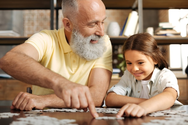 Favoriete spel. schattige petite pre-tiener meisje zit aan de tafel met haar grootvader en assembleert een legpuzzel met hem terwijl de man haar liefdevol bekijkt