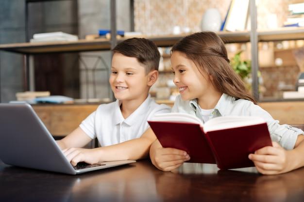 Favoriete tijdverdrijf. mooi klein meisje zit aan het boek en leest een boek, werpt nieuwsgierige blikken op de laptop terwijl haar broer er een spel op speelt