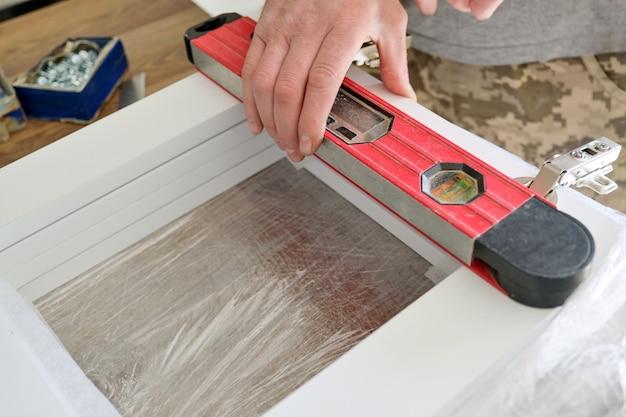 Fcloseup van arbeidershand met professionele hulpmiddelen en meubeldetails