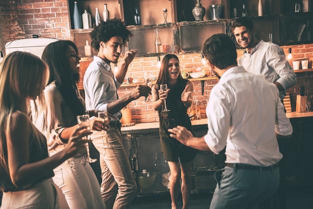 Feest dat nooit eindigt. vrolijke jonge mensen dansen en drinken terwijl ze genieten van een thuisfeest in de keuken