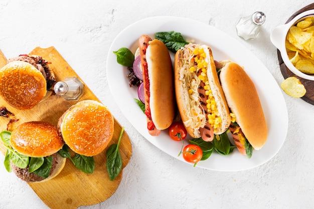 Feest eettafel met verschillende zelfgemaakte hotdogs en hamburgers bovenaanzicht