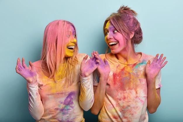 Feest en gekleurd vakantieconcept. optimistische europese vrouwen steken hun hand op en praten vrolijk over iets, hebben samen plezier, spelen met kleuren, uiten goede emoties. holifestival in india