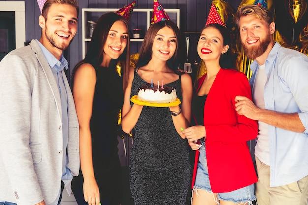 Feest hebben. jongeren rond verjaardagstaart. rondom de vrouw wachten gasten op de viering