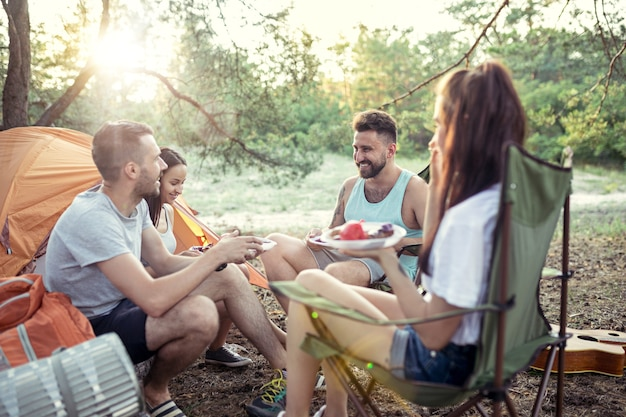 Feest, kamperen van mannen en vrouwengroep in het bos. ze ontspannen en eten barbecue tegen groen gras. het concept van vakantie, zomer, avontuur, levensstijl, picknick